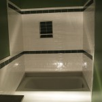 Downstairs bathroom after tiling with white and green glass subway tile