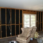 living room deconstruction, drywall and insulation removed on exterior walls to upgrade insulation