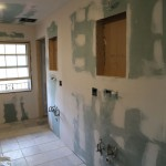 Drywall in place with holes for medicine cabinets'