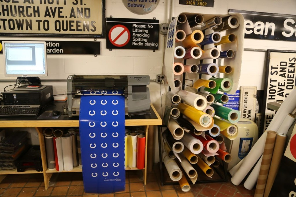 Rolls of vinyl in various colors ready for the printer. C line buttons being printed.