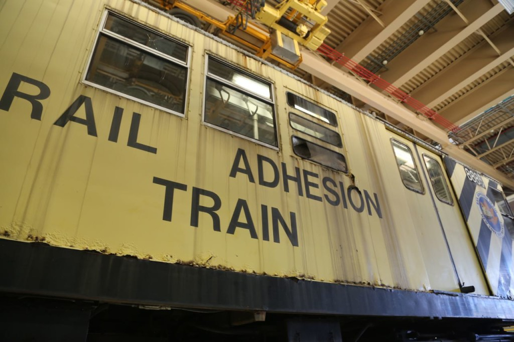 An old rail car that was converted to a rail adhesion train, used to add sand or a coating when leaves start to coat the rails. It is no longer, or rarely used, as contractors are hired to clear the rails of leaves.