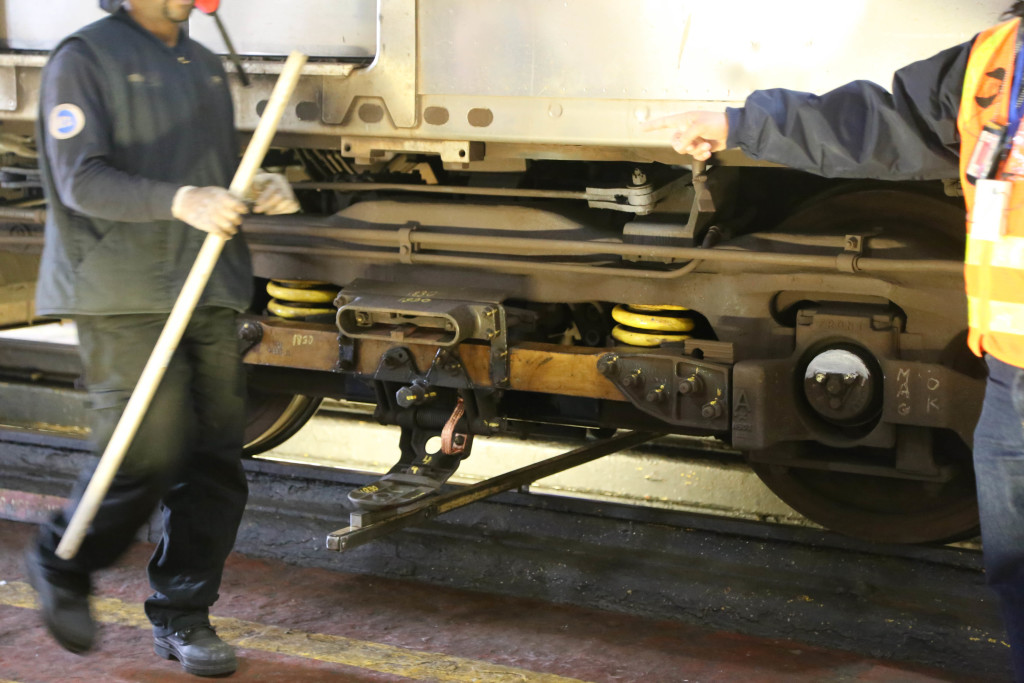 A stick is used to make sure the contact shoe is at the right height. A maintenance worker is carrying another stick used to measure the height of the car above the rail.