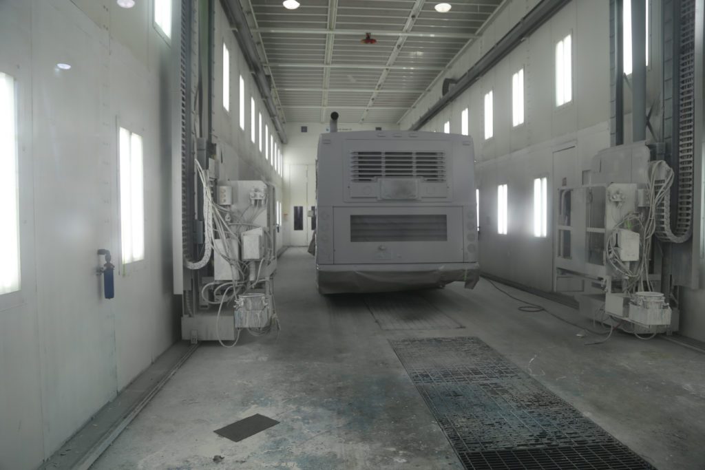 Bus in paint booth. Machine on wall is a platform with spray gun for a painter to paint from.