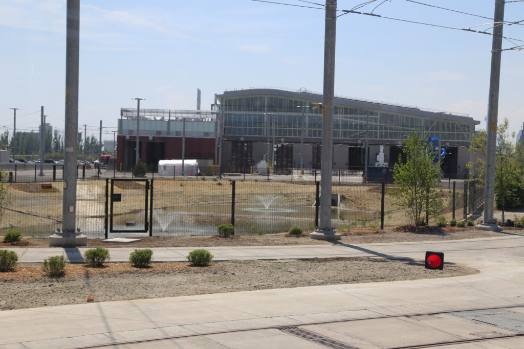 Stormwater retention pond in middle of storage yard with facility in background