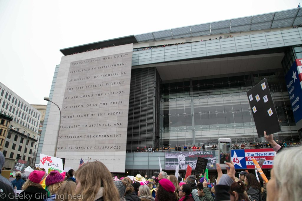 "An interesting contrast of people exercising their First Amendment Rights, in front of the Newseum with the First Amendment written on the side of the building with people cheering from the building with a ""Welcome President Trump"" sign"