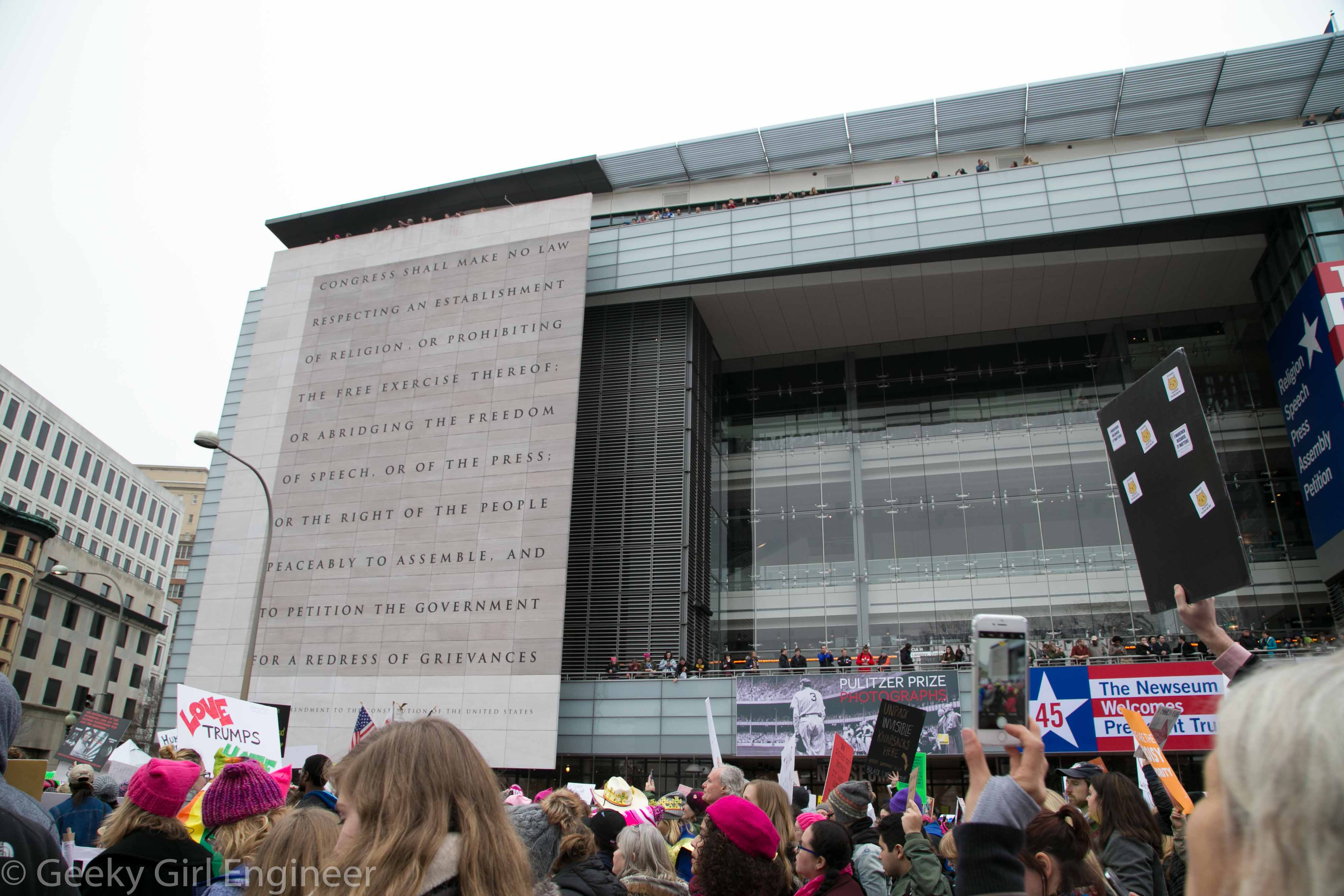 """An interesting contrast of people exercising their First Amendment Rights, in front  of the Newseum with the First Amendment written on the side of the building with people cheering from the building with a """"Welcome President Trump"""" sign"""